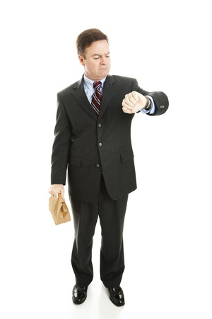 Businessman waiting for a ride to work, holding his lunch bag and checking the time.  Isolated on white.