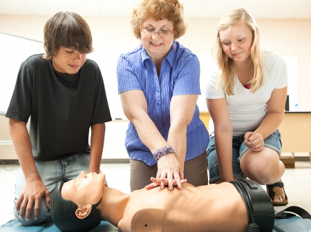 cpr: Teacher demonstrates CPR life saving techniques for her teenage students.   Stock Photo