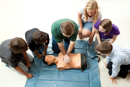learing: Group of teenagers learing CPR (cardiopulmonary resuscitation) in school.  Stock Photo