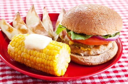 Healthy turkey burger on a whole grain bun, with baked potato wedges and corn on the cob, served on a red and white checkered tablecloth. photo