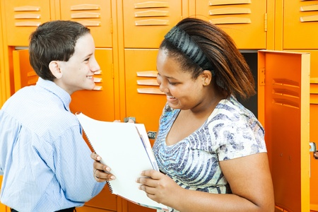 Middle school boy and girl talking together by the lockers.   photo