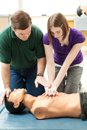 first class: Teen girl practicing CPR on a mannequin, with her teachers help.
