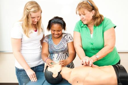 primeros auxilios: CPR, usando una m�scara de ox�geno en un maniqu� de aprendizaje de los estudiantes.