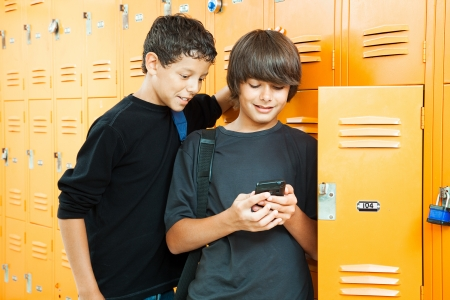 Two teenage boys playing a handheld video game in school by their lockers.