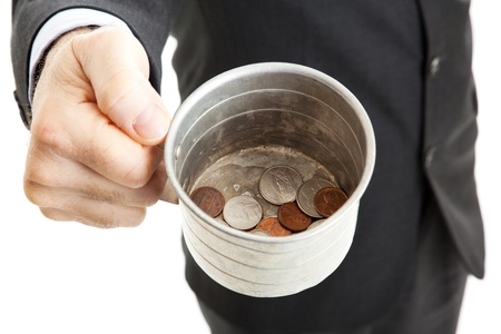 Closeup of a businessman with a tin cup, begging for change.  White background.   photo