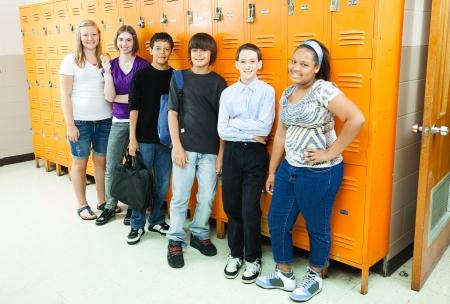 Groep van uiteenlopende middelbare scholieren door de school kluisjes.
