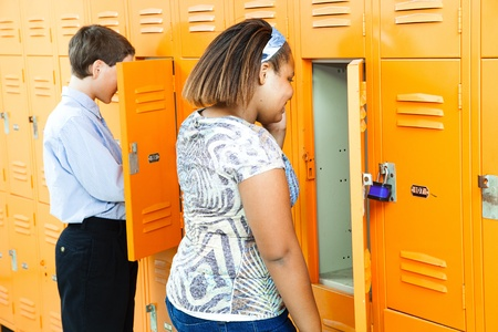 Middle school girl and boy at their lockers between classes.   photo
