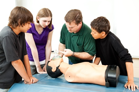 cardiopulmonary: Teacher demonstrates to students how to use an oxygen mask for CPR.