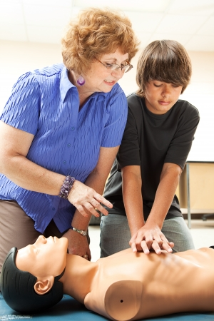 cpr: Teacher helping a teenage boy learn how to perform CPR. Stock Photo