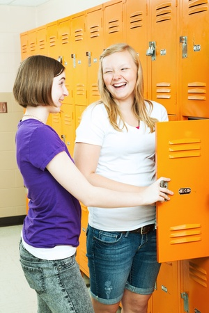 Two teenage girls talking by the lockers in the hallway of their high school.    photo