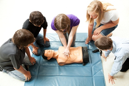 first floor: Teenage students use a mannequin to practice life saving techniques. Stock Photo
