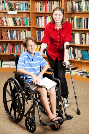 Disabled girl and boy in the school library.   Stockfoto