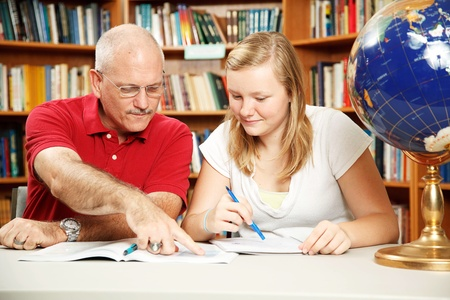 Father or teacher helping teen girl with homework.   photo