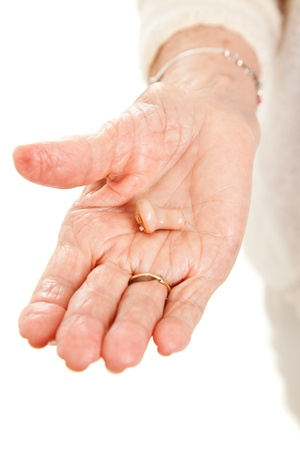 auditory: Closeup view of a hearing aid in the hand of a senior woman. Stock Photo
