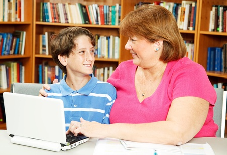 Mother or teacher, helping a little boy study in the library. Stock Photo - 10104134