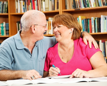 Mature couple has fun studying together at the library.   photo