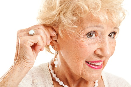 listening device: Closeup of a senior woman inserting a hearing aid in her hear.  Focus on the hearing aid.