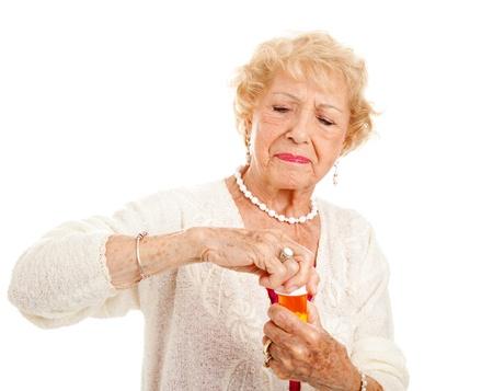artritis: Mujer senior con artritis se esfuerza por abrir una botella de medicamentos recetados.