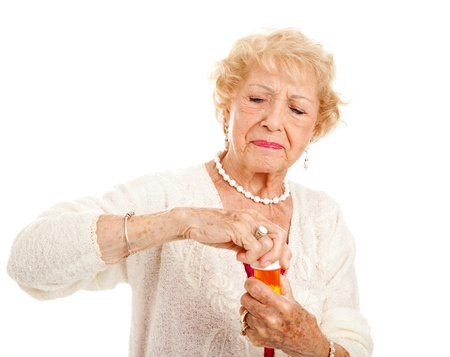 arthritis: Senior woman with arthritis struggles to open a bottle of prescription medication.