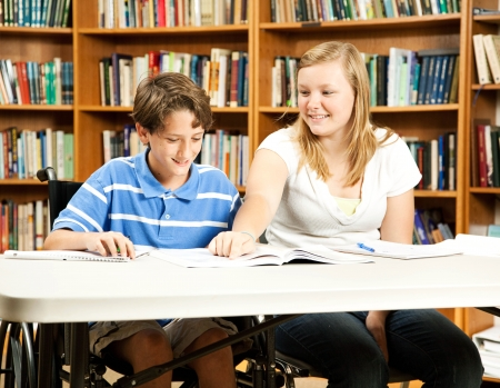 Teenage girl mentoring a younger, disabled boy in the school library.