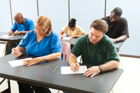 Classrom of adult education students taking a test in school .  Focus on the guy in the front.