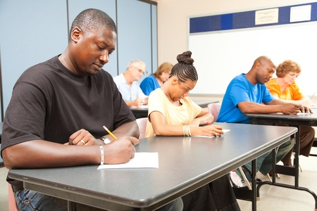 Class of adult college students taking a test.  Focus on guy in front left.