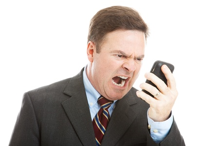 hostility: Angry businessman yelling into a cellphone.  Isolated on white.