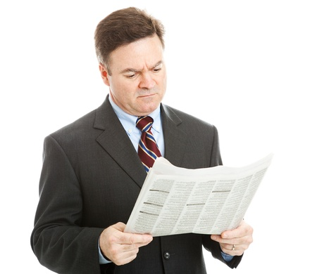 job hunt: Businessman reading bad news in the newspaper.  Could be financial or political news.  Isolated on white.   Stock Photo