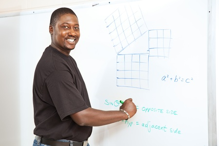 Handsome African-American college student (or teacher) doing trigonometry equations on the white board.   Stock Photo - 10179247