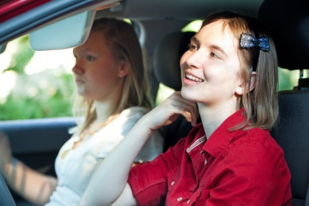 Teen girl is distracted, fixing her hair in the mirror, while driving the car.   photo