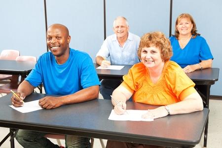 alumnos en clase: Feliz, diverso grupo de estudiantes de educación de adultos en clase.