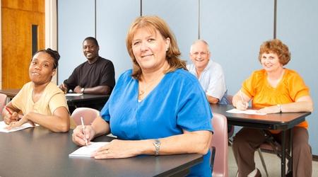 Mujer madura en la Universidad, entre un grupo de otros estudiantes adultos.   Orientación banner. Foto de archivo