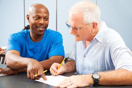 onderwijs: Jonge college student tutoring een oudere klasgenoot.