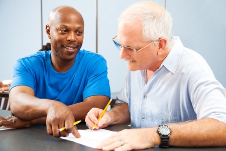 education help: Young college student tutoring an older classmate.   Stock Photo