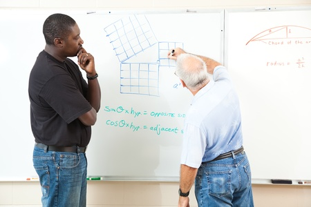 Teacher and adult student at the board working trigonometry equations.  Focus on the equations on the board. Stock Photo - 10320946