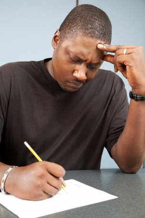 African-american adult education student struggles with test anxiety as he takes an exam. photo