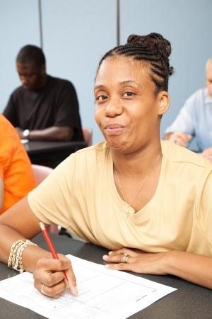 Mooie student met hersenverlamming, nemen een test in haar klasse volwassenenonderwijs.   Stockfoto