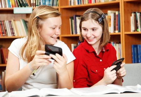 Two teenage girls texting in school, instead of studying.   photo