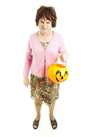 Embarassed father dressed up as a woman on Halloween, carrying a pumpkin bucket of candy.  Full body isolated on white. photo