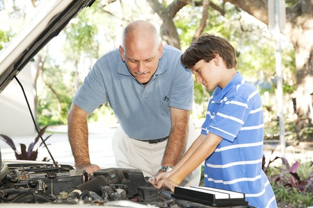 mend: Father teaching his son how to service and repair the car.