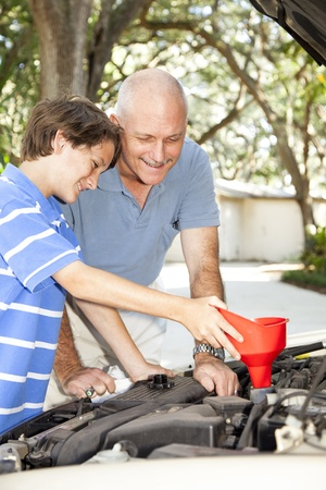 dirty car: Father and son changing the oil on the family car.   Stock Photo
