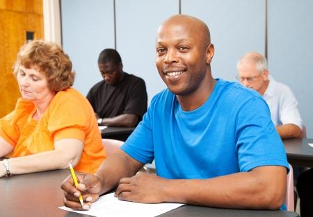 educacion: Retrato de un guapo estudiante afroamericano en clase de educaci�n de adultos.