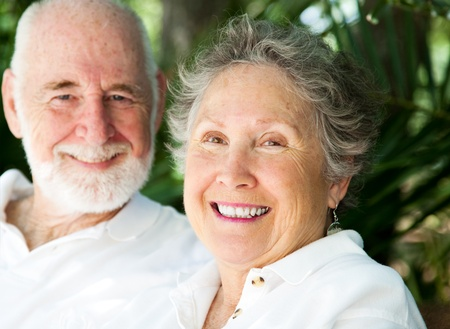 Portrait of a happy senior woman with her loving husband in background.   photo