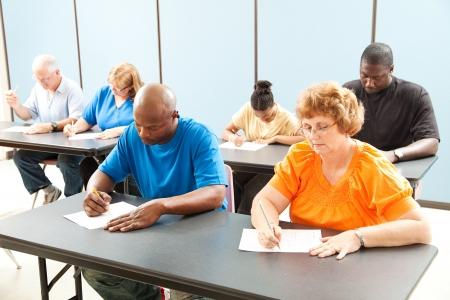 Divers volwassenenonderwijs klasse nemen een test in de klas.   Stockfoto