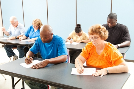 Diverse adult education class taking a test in the classroom.
