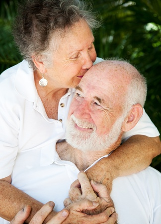 affection: Senior woman giving her husband a kiss on the forehead.