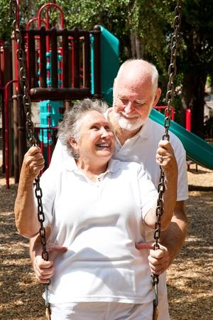Senior couple on a playground, swinging on the swingset.   Standard-Bild