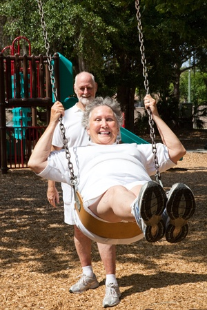Senior woman swinging on the playground in the park.  Her husband is pushing her.   Stock Photo