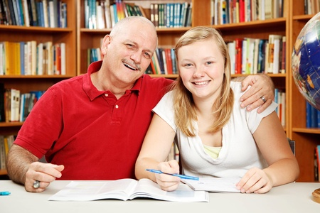 father teaching daughter: Teenage daughter studying with her father (or teacher) in the school library.