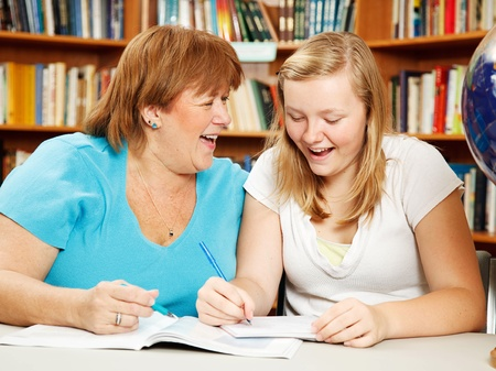 overweight students: Teen girl in the library studying with her mother (or teacher.) Stock Photo